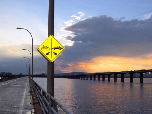 Placa apontando bicicleta na ponte carro no rio