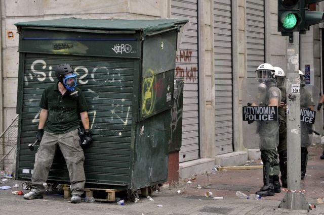 hoeme escondido atras de uma lixeira indoa taar policia de choque